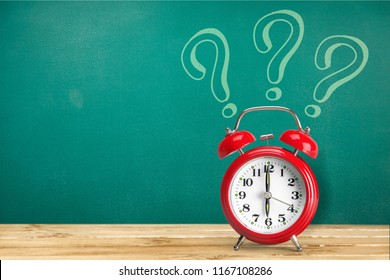 alarm clock on a background of a chalk drawn question on a chalkboard. copy space