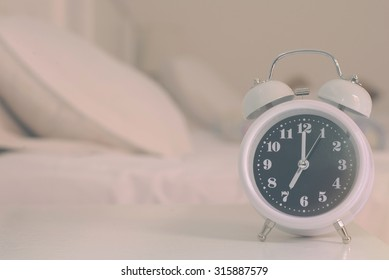 alarm clock on the bed in bedroom, retro style.