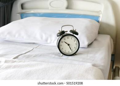 alarm clock on bed in hospital ward room background.