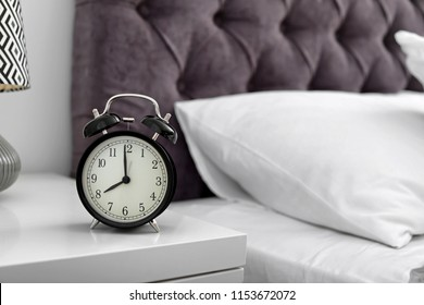 Alarm clock on bedside table. Time to wake up