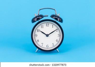 Alarm clock on blue background. Selective focus.