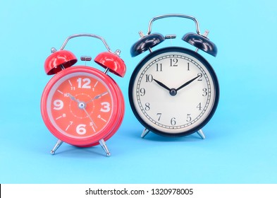 Alarm clock on blue background. Selective focus.
