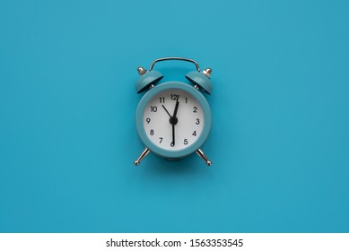 Alarm clock on blue background. Top view. Flat lay