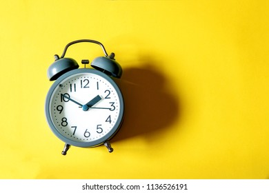 Alarm clock on bright  yellow background , time management concept