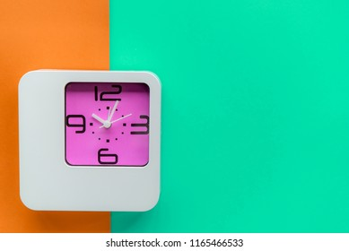 Alarm clock on colorful paper background