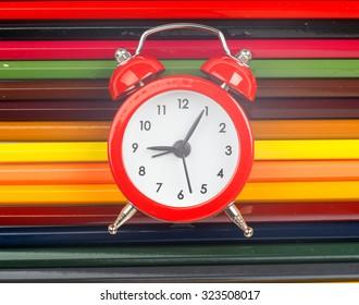 Alarm clock on crayons, close up view
