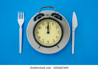 Alarm clock on a dish on a blue background. The concept of food through time.