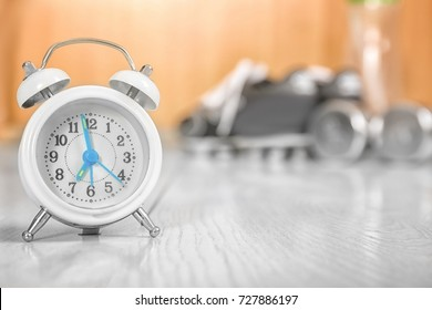 Alarm clock on floor indoors. Morning routine concept