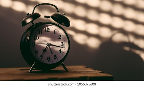 Alarm clock on night table in bedroom ticking time in early morning with sunlight and shadows on the wall in background