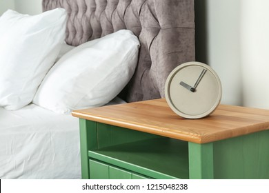 Alarm clock on nightstand in bedroom, space for text. Time management
