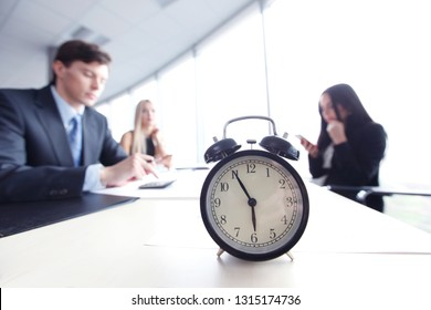 Alarm clock on office table with business discussion people group or meeting team background