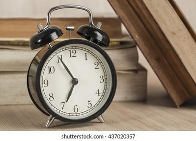 Alarm clock on old books background