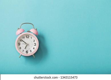 alarm clock on pastel paper background