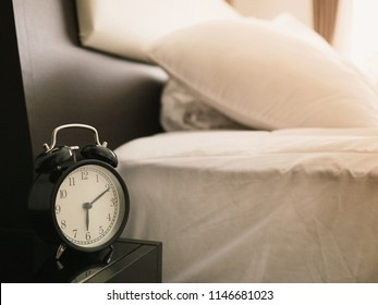 alarm clock on table beside the bedroom in the morning on working day