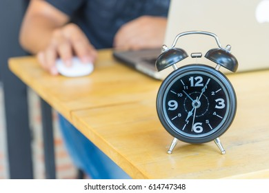 Alarm clock on table with blurred business man,