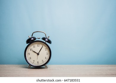 alarm clock on table front mint blue background