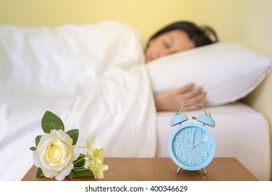 alarm clock on table and woman sleeping in background. (lens blur effect)