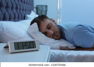 Alarm clock on table and young man sleeping in bed at night