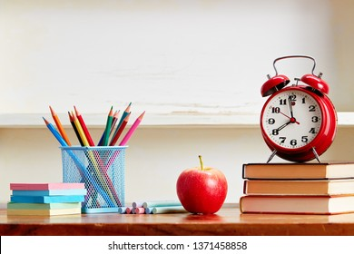 Alarm clock on top of books with school supplies on wooden table. Back to school conceptual image.