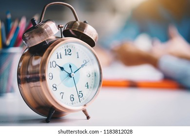Alarm clock on white table background with business people at meeting room.Time management and punctuality at work concept.