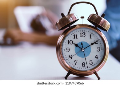 Alarm clock on white table background with businessman working with laptop.Time management and punctuality at work concept.