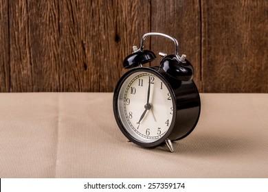 Alarm clock on wood background.