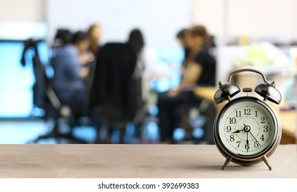 Alarm clock on wood with blurred abstract background of business discussion people group or  meeting team,time concept at early morning or Overtime in evening