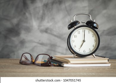 Alarm clock on wood table with school supplies , back to school concept