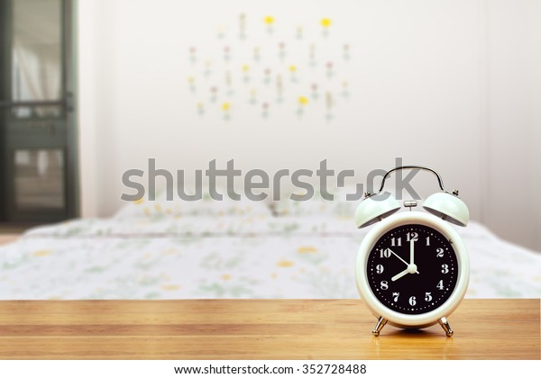 alarm clock on wooden floor over blurred image of bed room , businessman should be time management to relax and sleep concept