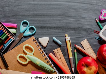 Alarm clock on wooden table on blackboard background