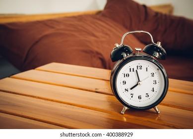 Alarm clock on wooden table in bedroom