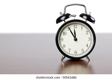 the alarm clock on wooden table