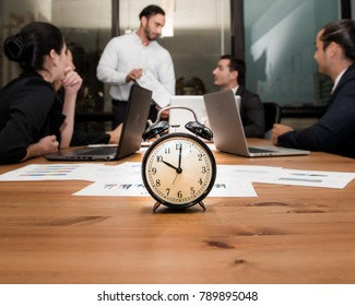 Alarm clock on wooden table with business discussion people group or meeting team background,Retro alarm clock in 10 o'clock ,Time concept at early morning or overtime in evening,