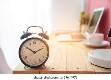 Alarm clock on work tale deadline time business concept. Alarm awake reminder appointment time agenda. selective focus clock on wooden table with coffee cup and laptop with soft sunlight.