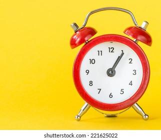 Alarm clock on yellow background