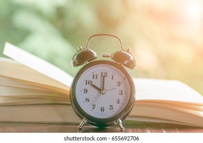 Alarm clock with open book in morning light background