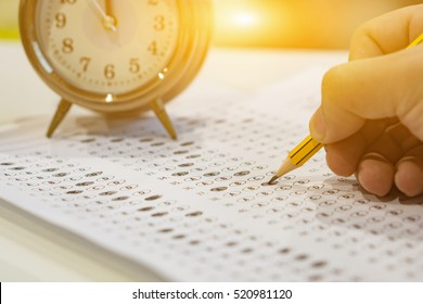 alarm clock, optical form of standardized test with bubbled and a black pencil examination,Answer sheet,education concept,selective focus,vintage