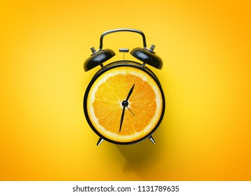 Alarm Clock of Orange Fruit on Yellow Background