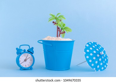 Alarm, clock, paper umbrella, small bucket full of sand and palm tree against pastel blue background. Summer and beach minimal concepts.