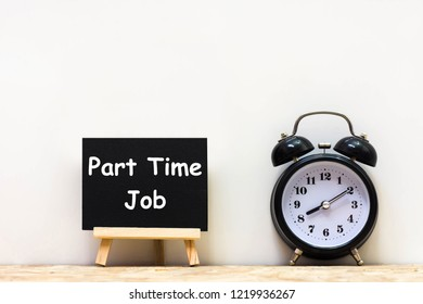 Alarm clock and Part Time Job words blackboard on desk white background. Chalkboard write No regular work on table for copy space.