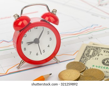 Alarm clock with pencil on business documents background