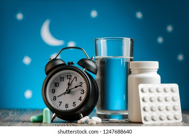 Alarm clock, pills and earplugs on night sky background. Insomnia, hygiene and recovery of sleep cycle.