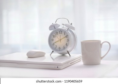 Alarm clock is placed on the laptop and the morning coffee cup.