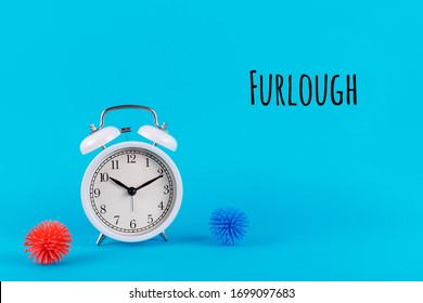 Alarm clock and plastic balls as viruses on the blue background with Furlough wording. Epidemic, social isolation, coronavirus COVID-19 concept. Option with text