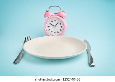 Alarm clock and plate with cutlery. Concept of intermittent fasting, lunchtime, diet and weight loss