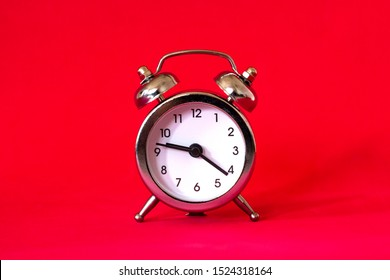 Alarm clock in retro vintage style on red background. Minimal modern style.