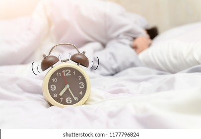 alarm clock ringing on bed and kid is under blanket on background, lazy concept