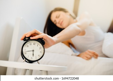Alarm clock ringing,annoyed woman waking up in early morning for work.Sleeping disorder.Tired woman oversleeping,bad sleep quality.Sleep deprived.Bad mood after dreaming nightmares.Insomnia