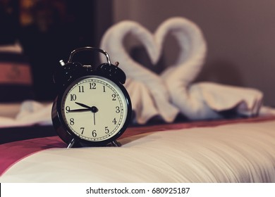 The alarm clock in the room shows couple lovers time with swan towel background