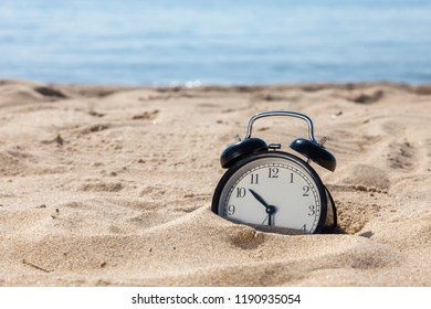 Alarm clock in sand and sea background. Summer vacation time concept.
